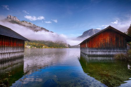 Misty morning on the lake Altausseer See. Foggy autumn scene in the morning. Location: resort Altausseer see, Liezen District of Styria, Austria, Alps. Europe.