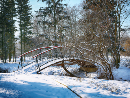 Winter frosty trees and old snowy bridge in the winter park. Winter nature with winter snowy trees