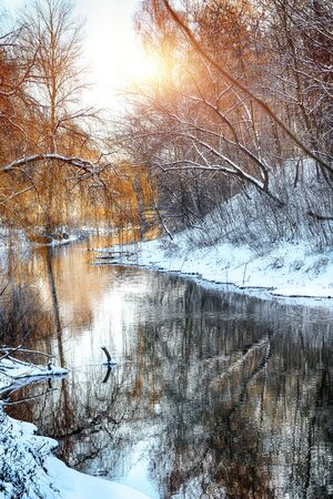 Winter landscape by a river in the sunset. Mirror reflection