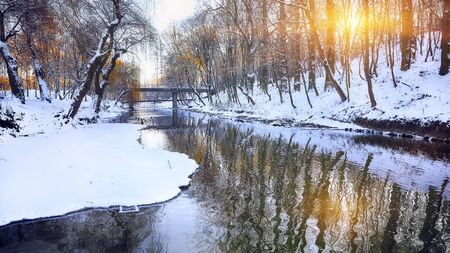 Winter landscape by a river. Mirror reflection