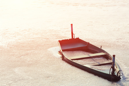 Frozen Into Ice Of River, Lake, Pond Old Wooden Boat. Abandoned Rowing Fishing Boat In Winter River. Forsaken Boat