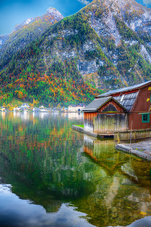 Sunny autumnal day at famous Hallstatt lakeside town reflecting in Hallstattersee lake. Location: resort village Hallstatt, Salzkammergut region, Austria, Alps. Europe.. Location: resort village Hallstatt, Salzkammergut region, Austria, Alps. Europe.
