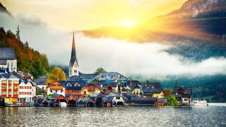 Toneel mening van beroemd Hallstatt-bergdorp met Hallstatter-meer. Mistige de herfstzonsopgang op Hallstatt-meer. Locatie: vakantieoord Hallstatt, regio Salzkammergut, Oostenrijk, Alpen. Europa.