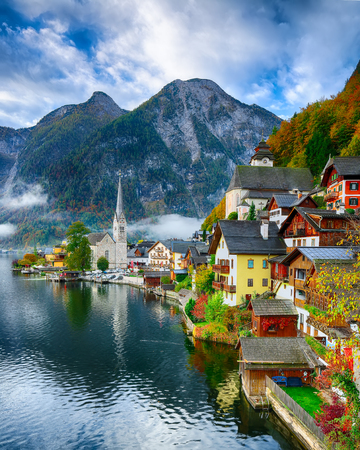 Foggy autumnal sunrise at famous Hallstatt lakeside town reflecting in Hallstattersee lake. Location: resort village Hallstatt, Salzkammergut region, Austria, Alps. Europe.. Location: resort village Hallstatt, Salzkammergut region, Austria, Alps. Europe.