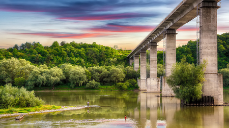 Huge arch  bridge built over Dnister river in Ukraine. Beautiful clouds in the sky over the river in Dnister Canyon. Ukraine. Europe Archivio Fotografico