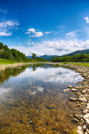 Mountain river stream of water in the rocks with blue sky and mirror reflection in water. Clear river with rocks leads towards mountains lit by sun. Carpathian region. Ukraine