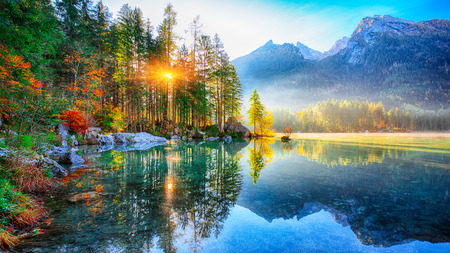 Fantastic autumn sunrise of Hintersee lake. Beautiful scene of trees near turquoise water of Hintersee lake. Location: resort Ramsau, National park Berchtesgadener Land, Upper Bavaria, Germany Alps, Europe