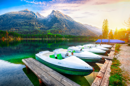Fantastic autumn evening at Hintersee lake. Few boats on the lake with turquoise water of Hintersee lake. Location: resort Ramsau, National park Berchtesgadener Land, Upper Bavaria, Germany Alps, Europe