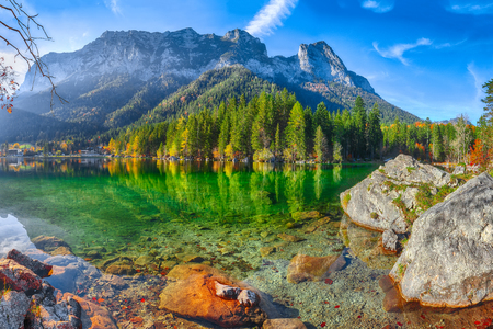 Fantastic autumn sunny day on Hintersee lake. Beautiful scene of mirror reflection in water of Hintersee lake. Location: resort Ramsau, National park Berchtesgadener Land, Upper Bavaria, Germany Alps, Europe