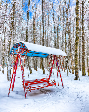 Empty swing in winter time with snow. Children's swing under a thick layer of snow