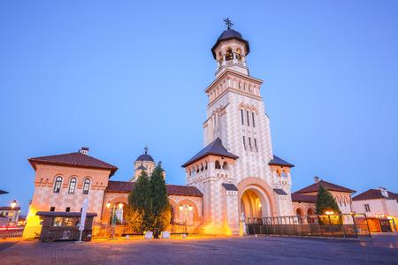 The Coronation Orthodox Cathedral and Roman Catholic cathedral in Fortress of Alba Iulia. Dramatic  evening summer scene of Transylvania, Alba Iulia city, Romania, Europe 版權商用圖片 - 119523574