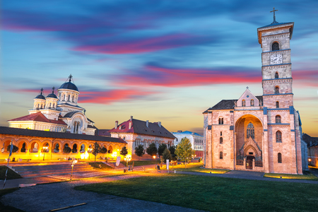 The Coronation Orthodox Cathedral and Roman Catholic cathedral in Fortress of Alba Iulia. Dramatic  evening summer scene of Transylvania, Alba Iulia city, Romania, Europe