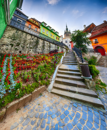 Stunning summer view of medieval city. Stairs leading to Sighisoara city and Clock Tower built by Saxons, Transylvania, Romania, Europe Foto de archivo