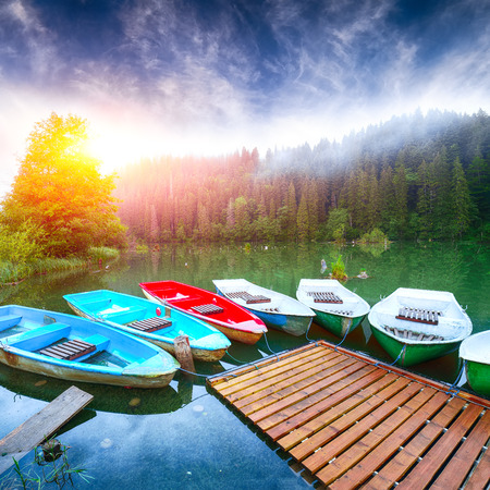 Boats on majestic mountain lake Lacul Rosu or Red Lake or Killer Lake. Splendid foggy summer scene of lake Lacul Rosu in Harghita County, Eastern Carpathians, Romania, Europe 免版税图像