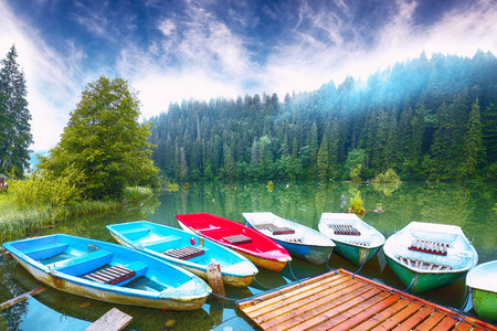 Boats on majestic mountain lake Lacul Rosu or Red Lake or Killer Lake. Splendid foggy summer scene of lake Lacul Rosu in Harghita County, Eastern Carpathians, Romania, Europe 版權商用圖片
