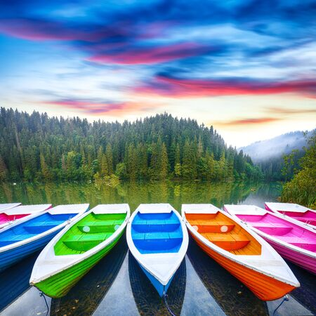 Boats on majestic mountain lake Lacul Rosu or Red Lake or Killer Lake. Splendid foggy summer scene of lake Lacul Rosu in Harghita County, Eastern Carpathians, Romania, Europe 스톡 콘텐츠