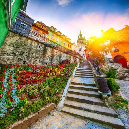 Stunning summer view of medieval city. Stairs leading to Sighisoara city and Clock Tower built by Saxons, Transylvania, Romania, Europe Foto de archivo - 132529897