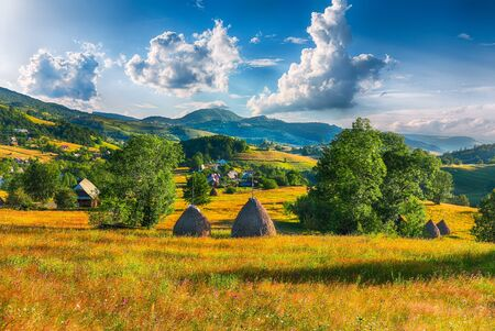 Beautiful countryside landscape with forested hills and haystacks on a grassy rural field in mountains. Scene in Rogojel village of Cluj County, Romania, Europe Foto de archivo - 132529930