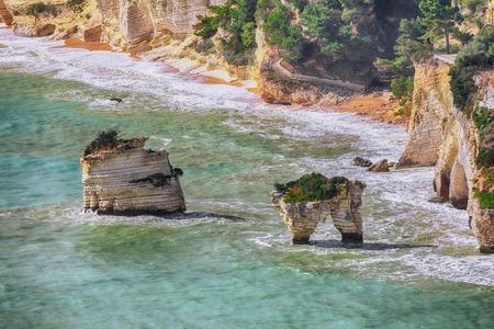 Picturesque islets Faraglioni di Puglia in summer Adriatic sea bay Baia Delle Zagare. Mattinata Faraglioni stacks and beach coast of Mergoli, Vieste Gargano, Apulia, Italy. Europe