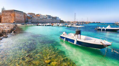 Plusieurs bateaux de pêche au port d'Otrante - ville côtière des Pouilles avec une mer turquoise. vacances italiennes. Ville Otranto, province de Lecce dans la péninsule du Salento, Pouilles, Italie Banque d'images