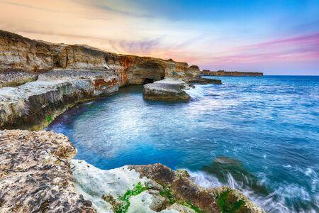 Picturesque seascape with cliffs rocky arch and stacks (faraglioni) at Torre Sant Andrea, Salento coast, Puglia region, Italy Foto de archivo - 134179731