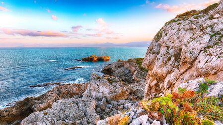Dramatic spring sunset on the the cape Milazzo panorama of nature reserve Piscina di Venere.  Location: cape Milazzo,  Island Sicilia, Italy, Europe. Mediterranean and Tyrrhenian sea Foto de archivo - 134179749