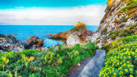 Dramatic spring sunset on the the cape Milazzo panorama of nature reserve Piscina di Venere.  Location: cape Milazzo,  Island Sicilia, Italy, Europe. Mediterranean and Tyrrhenian sea Foto de archivo - 134179795