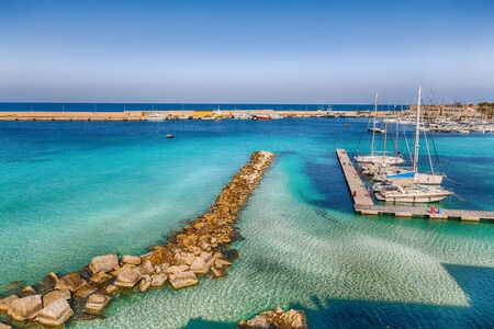 Several fishing boats at the Otranto harbour - coastal town in Puglia with turquoise sea. Italian vacation. Town Otranto, province of Lecce in the Salento peninsula, Puglia, Italy Foto de archivo - 134179820