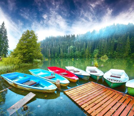 Boats on majestic mountain lake Lacul Rosu or Red Lake or Killer Lake. Splendid foggy summer scene of lake Lacul Rosu in Harghita County, Eastern Carpathians, Romania, Europe Foto de archivo - 134179822