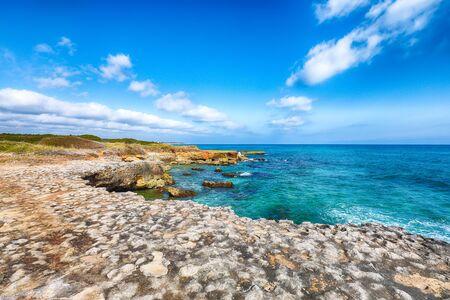 Picturesque seascape with white rocky cliffs, sea bay, islets and faraglioni near by Conca Specchiulla Beach, Salento Adriatic sea coast, Puglia, Italy Foto de archivo - 134179897