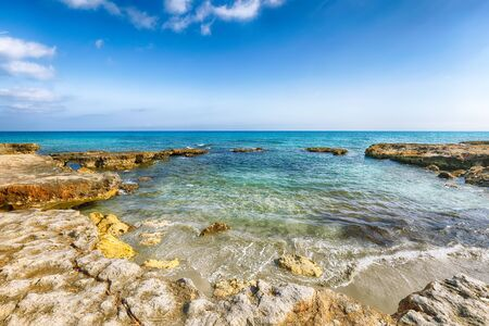 Picturesque seascape with white rocky cliffs, sea bay, islets and faraglioni near by Conca Specchiulla Beach, Salento Adriatic sea coast, Puglia, Italy Foto de archivo - 134180578