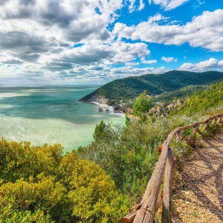 Picturesque islets Faraglioni di Puglia in summer Adriatic sea bay Baia Delle Zagare. Mattinata Faraglioni stacks and beach coast of Mergoli, Vieste Gargano, Apulia, Italy. Europe Foto de archivo - 134180701