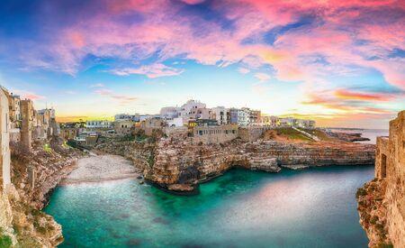 Sunset at Cala Paura gulf with Bastione di Santo Stefano and Lama Monachile beach in background. Polignano a Mare, Apulia, Italy, province of Bari. Foto de archivo - 134181325