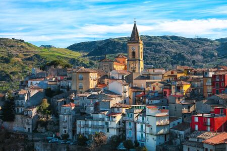 Panorama of the belltower and the village in the valley at sunrise. Mountain village Novara di Sicilia, Sicily, Italy Stockfoto
