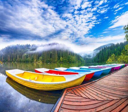 Boats on majestic mountain lake Lacul Rosu or Red Lake or Killer Lake. Splendid foggy summer scene of lake Lacul Rosu in Harghita County, Eastern Carpathians, Romania, Europe