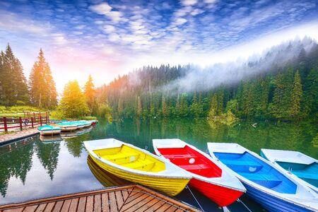 Boats on majestic mountain lake Lacul Rosu or Red Lake or Killer Lake. Splendid foggy summer scene of lake Lacul Rosu in Harghita County, Eastern Carpathians, Romania, Europe Reklamní fotografie