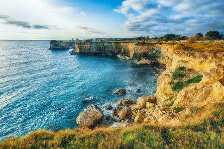 Picturesque seascape with cliffs rocky arch and stacks (faraglioni) at Torre Sant Andrea, Salento coast, Puglia region, Italy