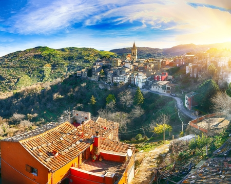Panorama of the belltower and the village in the valley at sunrise. Mountain village Novara di Sicilia, Sicily, Italy Reklamní fotografie