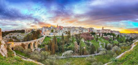 Gravina in Puglia ancient town, bridge and canyon at sunrise. Panoramic view of old city Gravina in Puglia, Apulia, Italy. Europe 스톡 콘텐츠