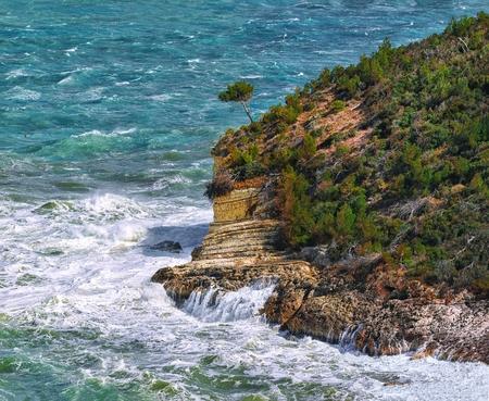 Above the cliffs at the coastline of Vieste. Summer rocky sea coast near Architello (Arch) of San Felice on the Gargano peninsula, Puglia, Italy Фото со стока