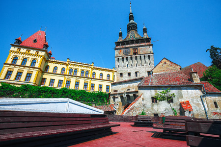 Famous clock tower build by Saxons in the nice  touristic city Sighisoara. Resting place with benches, Sighisoara, Transylvania, Romania, Europe