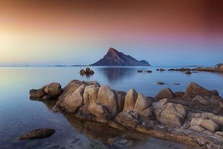Fantastic azure water with rocks near beach Porto Taverna at sunset. Location: Loiri Porto San Paolo, Olbia Tempio province, Sardinia, Italy, Europe