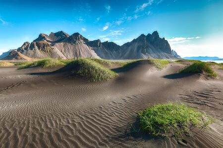 Dramatic sunny day and gorgeous rippled black sand beach and green grass on Stokksnes cape in Iceland. Stock fotó