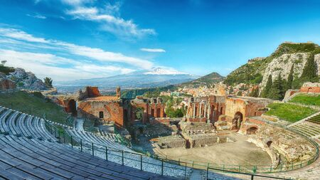 Ruins of ancient Greek theater in Taormina and Etna volcano in the background. Coast of Giardini-Naxos bay, Sicily, Italy, Europe. Stock Photo