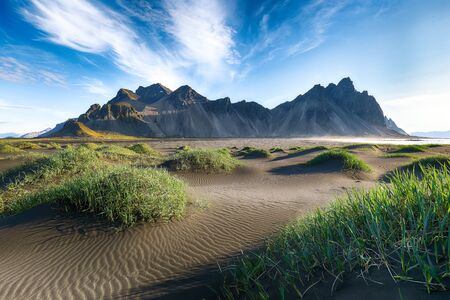 Fantastic sunny day and gorgeous black sand dunes on Stokksnes cape in Iceland. Imagens