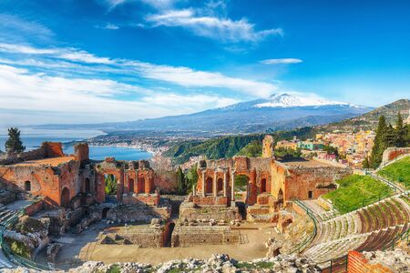 Ruins of ancient Greek theater in Taormina and Etna volcano in the background. Coast of Giardini-Naxos bay, Sicily, Italy, Europe. Foto de archivo