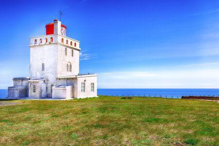 Landscape with white lighthouse at Cape Dyrholaey. Location: Cape Dyrholaey (Cape Portland), near Vik village, Island, Europe