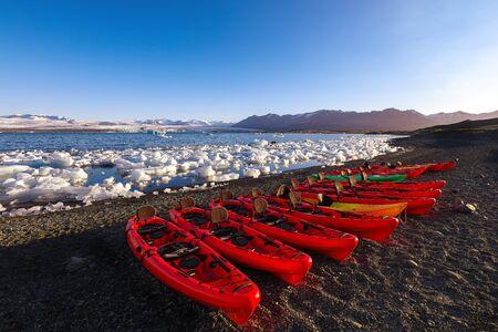 Kayaks on the shore of Jokulsarlon glacier lagoon at sunset. Location: Jokulsarlon glacial lagoon, Vatnajokull National Park, south Iceland, Europe Stockfoto - 128819488