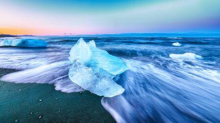 Des morceaux incroyables de l'iceberg scintillent sur la célèbre plage de diamants de la lagune de Jokulsarlon au coucher du soleil. Lieu : Lagon de Jokulsarlon, Diamond beach, parc national de Vatnajokull, Islande, Europe