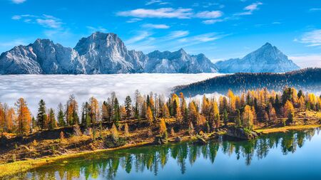Stunning aerial view of  crystal clear Lake Federa in Dolomites Alps under sunlight in mist and fog.  Location: Federa lake with Dolomites peak, Cortina DAmpezzo, South Tyrol, Dolomites, Italy, Europe